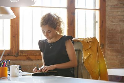 Businesswoman writing in book at desk