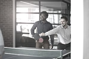 co-workers playing ping-pong in an office