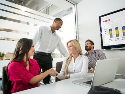 Four people meeting each other in a meeting room during an icebreaker game.