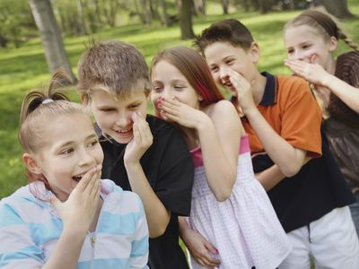 A Group Of Children Standing In A Row And Telling Secrets To Each Other