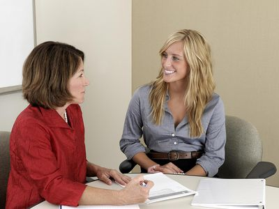 A business mentor working with a young employee on understanding a project in a conference room.