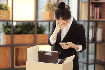 Disappointed Businesswoman Standing With Cardboard Box in Office