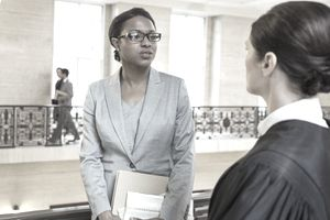 A law school graduate talking to a judge in a courthouse walkway hoping to get a job interview.