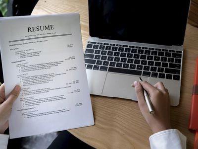 Image shows hands holding a multiple page resume, with a pen in one hand in front of a laptop.