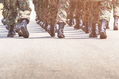 Low Section Of Army Soldiers Walking On Street During Parade
