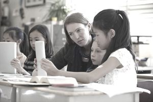 Students and teacher using digital tablets in class