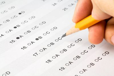 Hand filling in answers on a multiple choice test with a number two pencil.