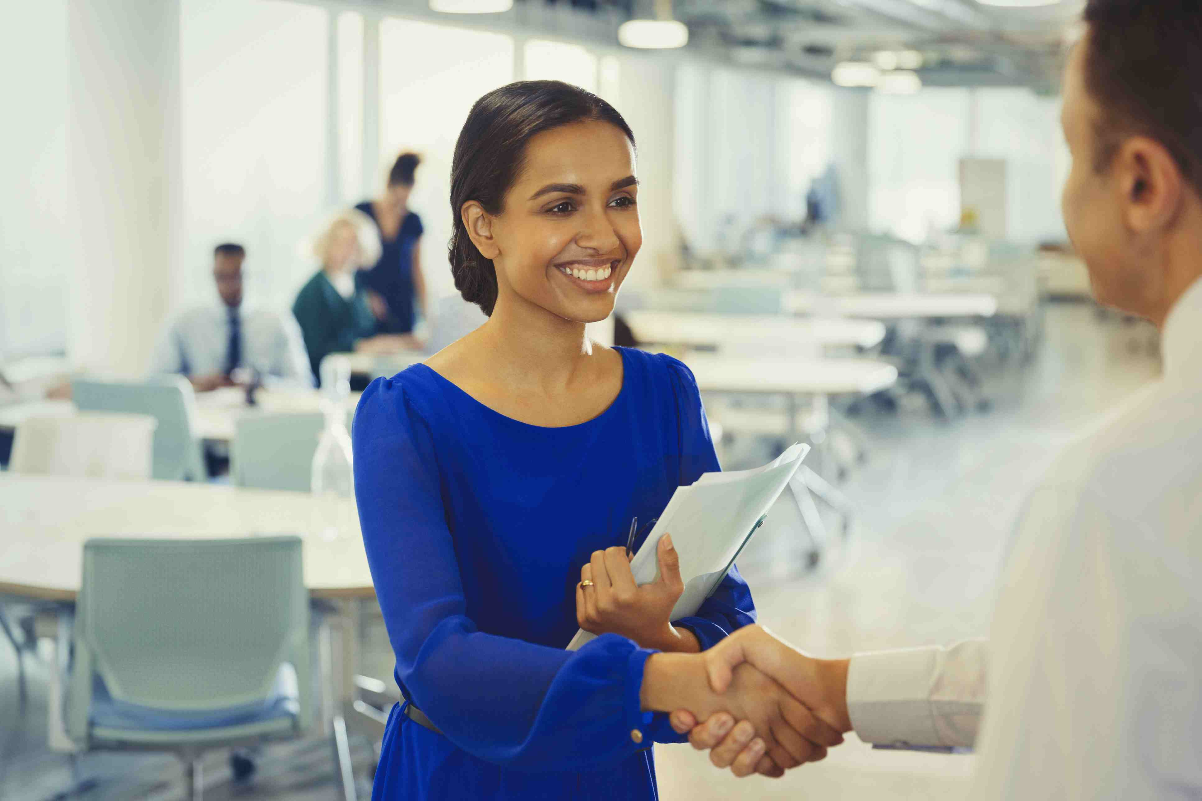 Smiling businesswoman shaking hands with businessman in office
