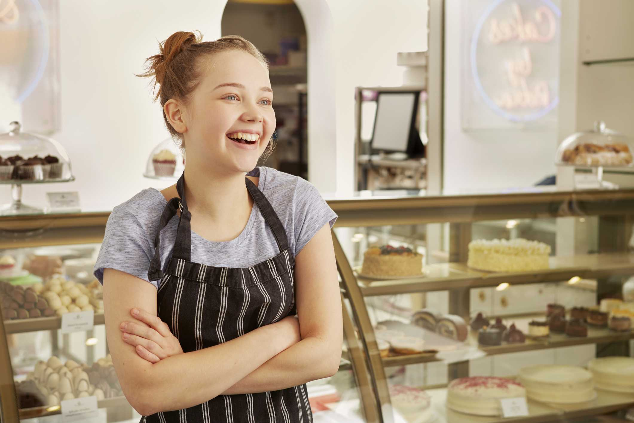 Young woman working at bakery and smiling