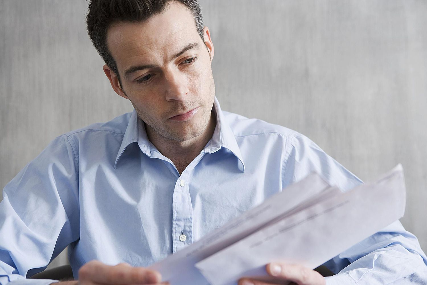 Man Looking at Letters of Rejection Which Are Disheartening