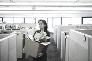 Young businesswoman carrying cardboard box in office, portrait