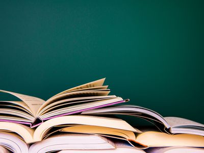 stack of open books against a wall