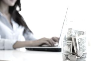 Woman in blue shirt working on laptop with jar of cash and coins