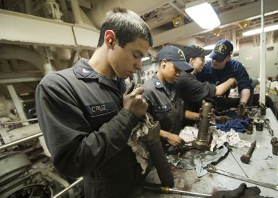 Engineman with Cruz on name tag repairing equipment in an engine room with three other workers