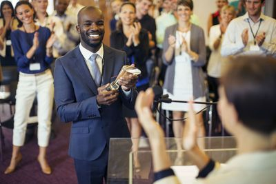 a businessman accepting an award in front of colleagues