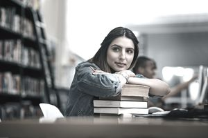 Young woman college student looking thoughtful in library.