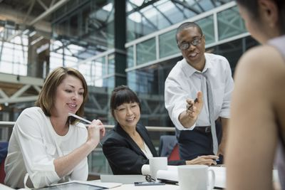 Manager working with group of employees during a meeting in an office conference area.