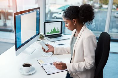 Woman working at desk with computer and phone