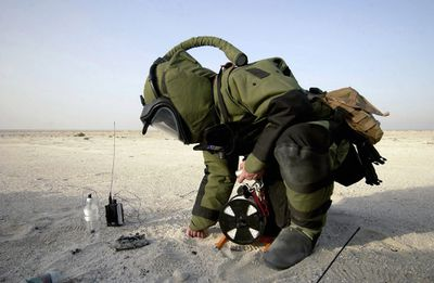Explosive Ordnance Disposal (EOD) Specialist wearing a heavy protective suit works on exploding ordnance in the field.