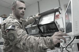 Sergeant in uniform checks medical equipment