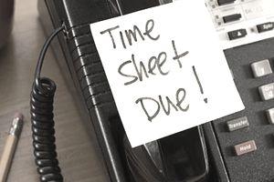 Time sheet due written on a sticky note stuck to a telephone