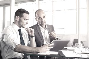 Two businessmen in an office looking at a laptop discussing forming a corporation.