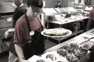 Boy working as a delivery person at a pizza buffet