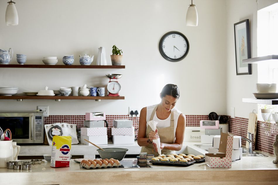 Woman icing cupcakes in kitchen