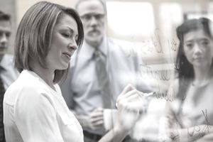 Businesswoman writing on glass in meeting