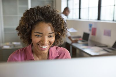 Woman smiles at how much she has been able to improve her productivity and stress level with these tips.