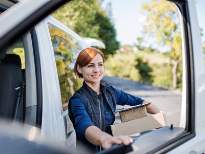 Young woman courier by a delivery car, carrying parcels.