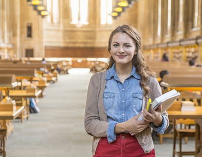 Law Student standing in library holding books