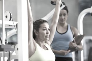 Woman exercising in health club with trainer