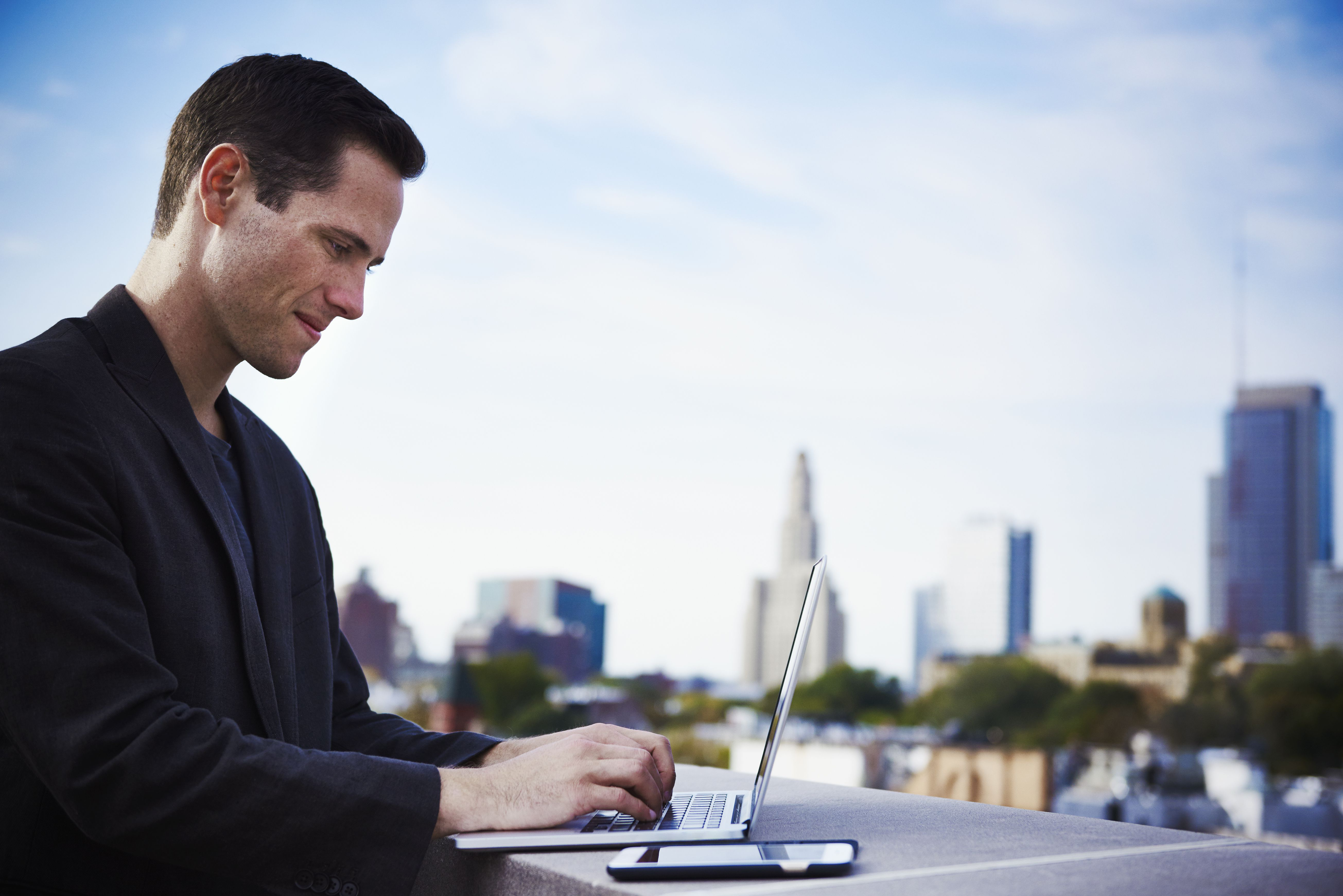 A young man standing on a rooftop working at an open laptop with a cellphone beside it.