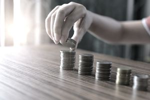 Boy Hand Put Coins To Stack Of Coins .savings, finances, economy and home concept