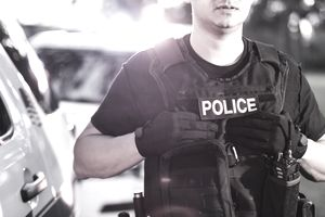 Hispanic police officer wearing bulletproof vest