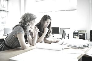 Businesswomen leaning on table discussing plans