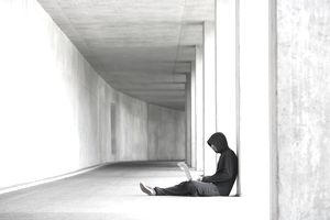 a long view of a man sitting in a hallway working on a laptop