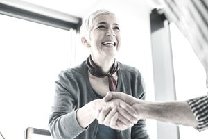 Business woman shaking hands with coworker