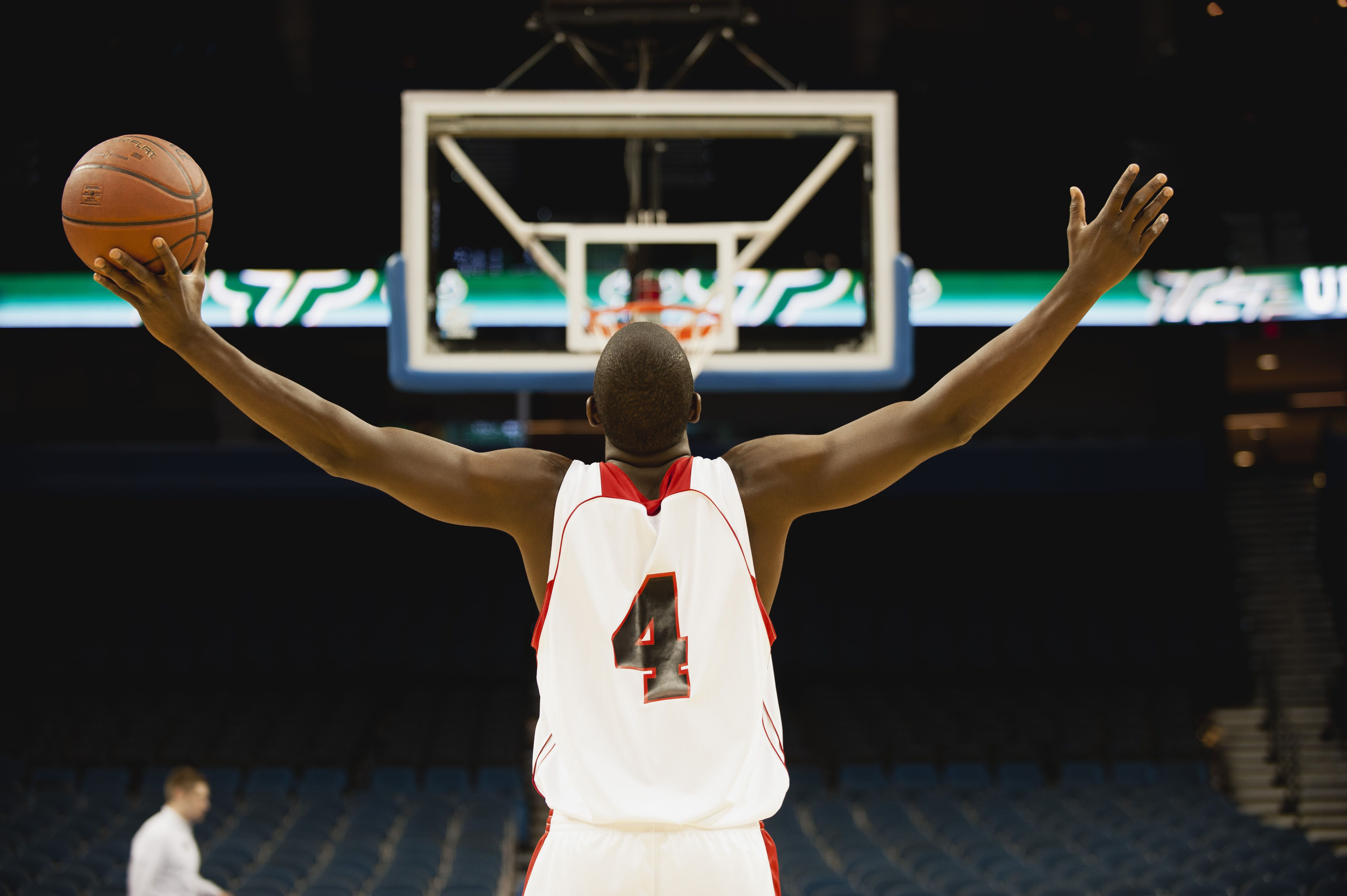 Basketball player standing in basketball court with arms outstretched, rear view