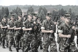Group of Marines Wearing Camouflage Marching With Rifles
