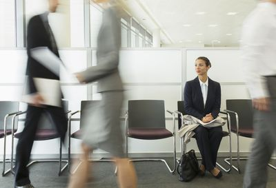 woman in suit waiting with people passiing