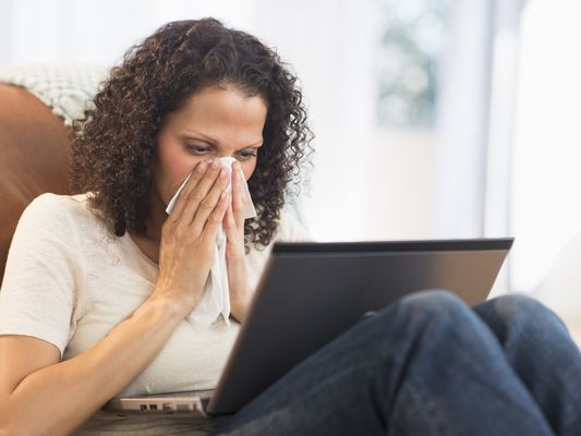 Woman sitting with laptop and blowing nose
