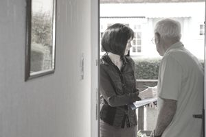 Researcher talking to elderly man on the doorstep