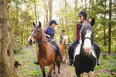 Therapeutic riding instructor with a student on horseback on a forest path.