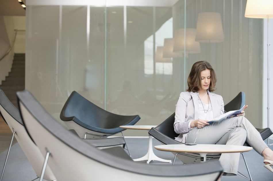 Businesswoman sitting on a chair and reading a magazine