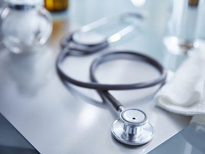 stethoscope on table with other medical items in background
