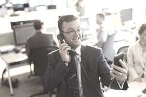 Playful businessman talking on telephone and taking selfie in office