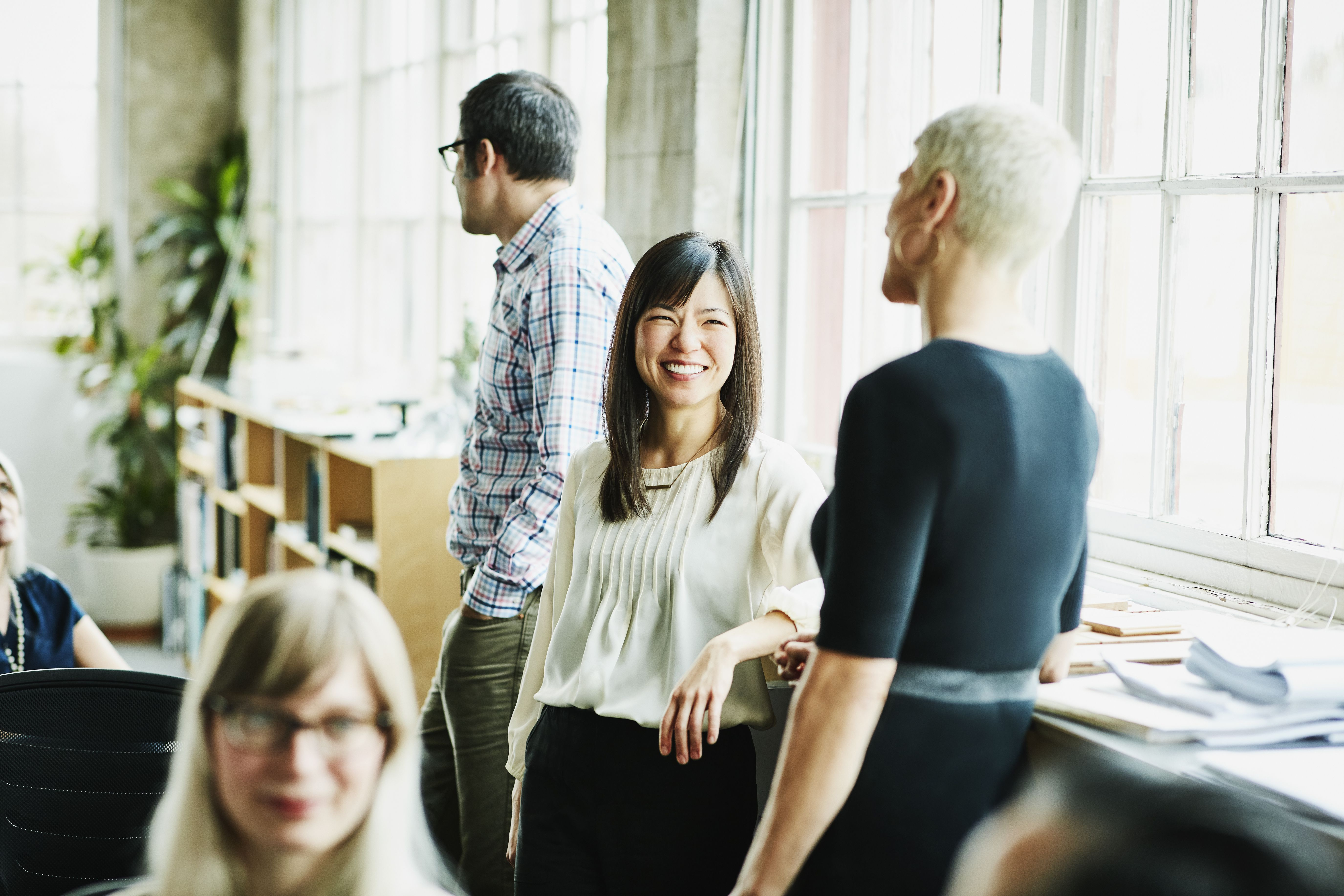 Smiling coworkers in discussion in design studio