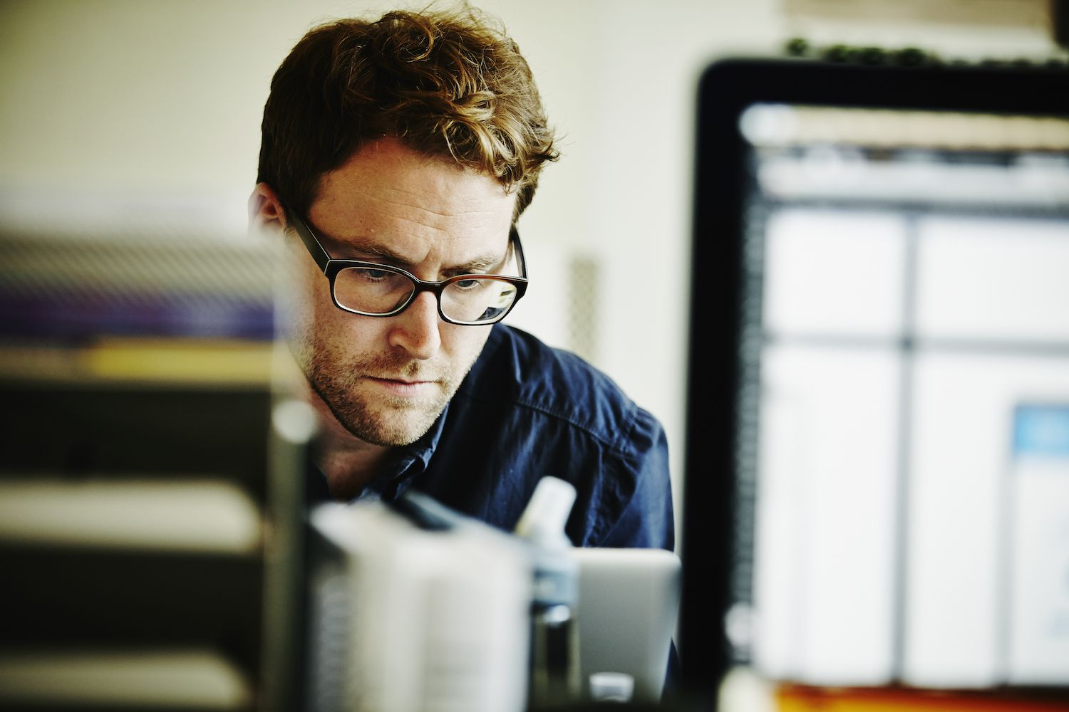 Man wearing glasses working intently on an art catalog.